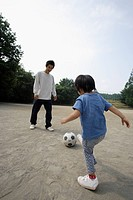 A young father playing football with his son