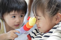 Sister and brother playing with a soft doll (thumbnail)