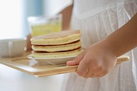 A child holding a tray with some pancakes