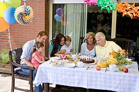 A multi_generational family celebrating a birthday, outdoors