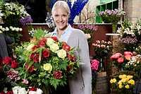 A woman holding a bouquet of flowers in a florists
