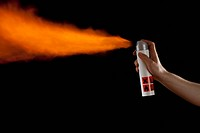 A hand spraying flames from an aerosol can, studio shot