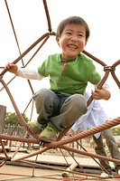 A small boy enjoying himself sitting in structure of ropes
