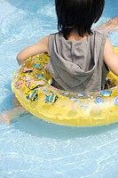 A boy holding a float in pool