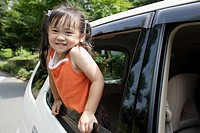 A girl leaning forward from a car window