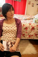A young woman holds a book as she sits near the bed