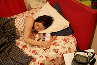 A young woman sleeps peacefully on the bed after reading a book
