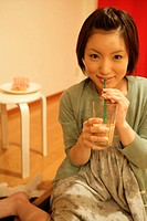 A young woman takes a sip from a glass as she smiles at the camera (thumbnail)