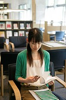 A young woman sits on the chair while she reads a book in the library (thumbnail)