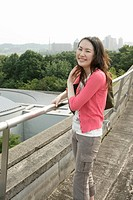 A young woman heartily smiles at the camera as she stands against the railing