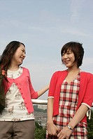 Two young women heartily share laughter as they stand against the railing (thumbnail)