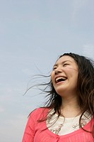 A young woman is seen under the sky as she laughs her way to glory