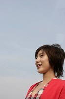 A young woman is seen under the sky as she smiles heartily (thumbnail)