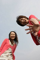 Low angle view of two young women showing their palms over the camera