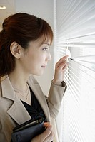 A woman looking outside through the blinds (thumbnail)
