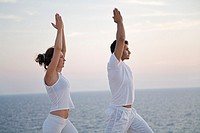 Couple doing yoga by the sea
