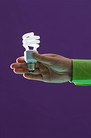 A hand holding out an energy saving light bulb