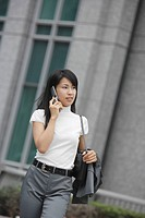 A woman moves on while conversing on the mobile phone