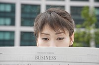 A woman attentively reading the newspaper (thumbnail)