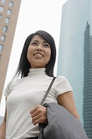 A woman smiling with skyscrapers at the background