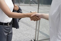 A midsection of two women seen shaking hands