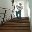 Low angle view of a businessman standing on a staircase with a file in his hand (thumbnail)