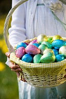 A young girl holding a basket full of Easter eggs