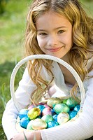 A portrait of a young girl holding a basket full of Easter eggs