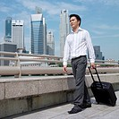 Low angle view of a businessman pulling a suitcase (thumbnail)