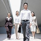 Portrait of a businessman walking with three businesswomen