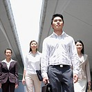 Low angle view of a businessman walking with three businesswomen