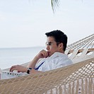 Side profile of a mid adult man lying in a hammock using a laptop