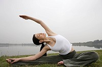 View of a young woman stretching out on the ground (thumbnail)
