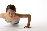 Portrait of a young woman exercising pushup