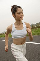 Side view of a young woman jogging on the road
