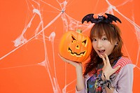 Close-up of teenage girl holding jack-o-lantern (thumbnail)