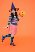 View of a teenage girl holding jack_o_lantern