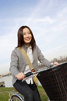 View of a cheerful young woman riding a bicycle