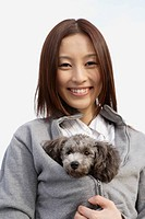 Portrait of a young woman holding her pet dog inside her jacket