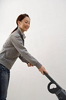Side view of a young woman using a vacuum cleaner