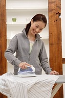 View of a young woman ironing a shirt (thumbnail)