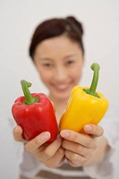 View of a young woman with bell peppers in her hands