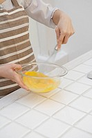Close_up of hands mixing egg yolk with whisk