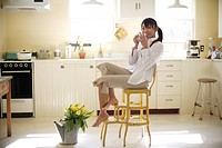 View of a woman sitting on chair in kitchen