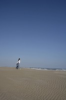 Rear view of a young woman walking on sand near the shore