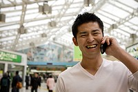 A smiling young man using cellphone (thumbnail)