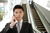Portrait of a young businessman using mobile phone