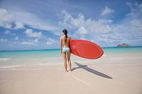 A woman standing on beach with surfboard in hand (thumbnail)