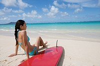 A woman sitting on beach with surfboard (thumbnail)