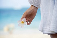 A woman standing on beach with flower in hand